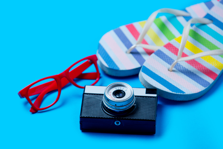 comprando zapatos: colorful sandals, glasses and camera on the wonderful blue background