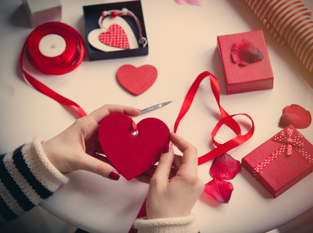 white caucasian hands wrapping heart shaped toy on the wonderful things for decoration background
