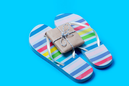 colorful sandals and cute small gift on the wonderful blue background
