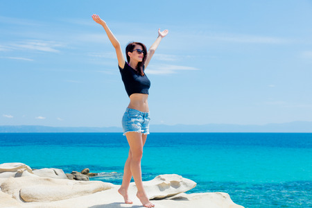 sunbath: beautiful young woman standing on the wonderful sea background in greece