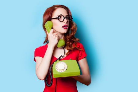 beautiful surprised young woman with retro phone on the wonderful blue background Stock Photo