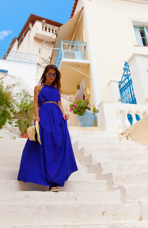 photo of beautiful young woman standing on the stairs near house in Greece