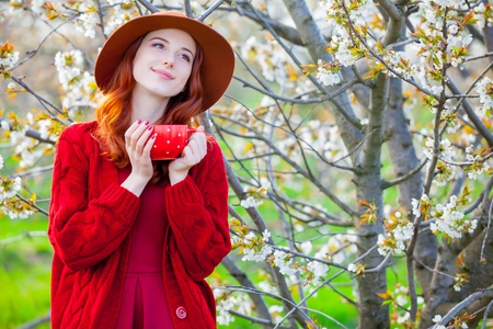 beautiful young woman with cup of coffee on the wonderful blooming trees background
