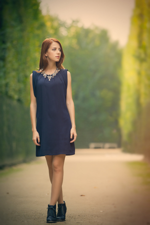 dress form: beautiful young woman standing in the park full of bushes Stock Photo