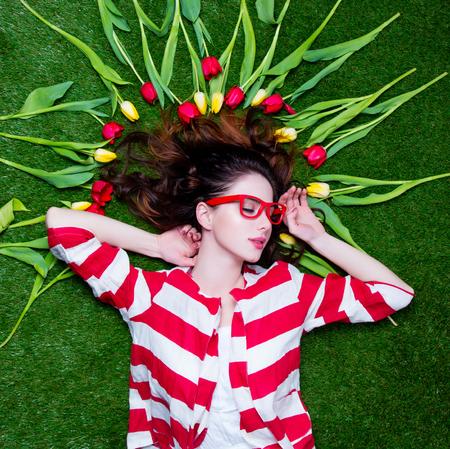 素晴らしい緑の芝生背景に横たわっている黄色と赤のチューリップに近い美しい若い女性 写真素材