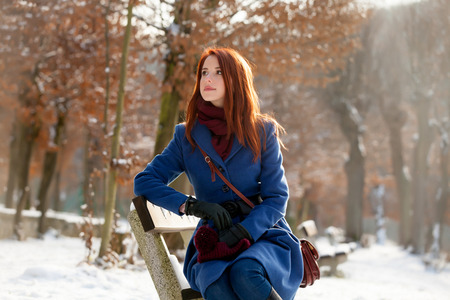 photo of beautiful young woman sitting on the bench in the park in winter Stock Photo