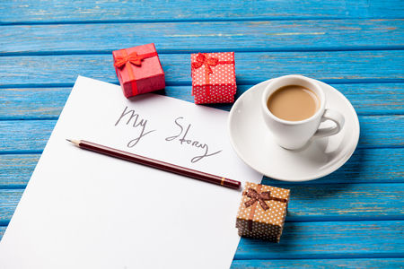 caja de leche: photo of paper My story, cute gifts and cup of coffee on the wonderful blue wooden background