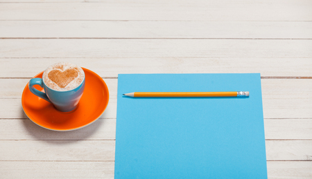 photo of beautiful blue cup of coffee and sheet of paper with pencil on the wonderful white wooden background
