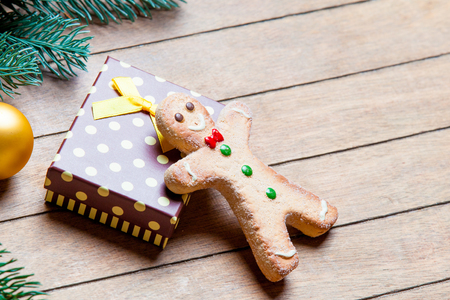 gingerbread man: gift, gingerbread man and fir tree branch with bauble on the wonderful brown wooden background