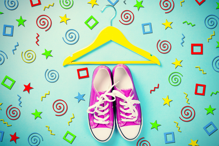 shoelace: hanger and purple gumshoes on the wonderful blue background in art pop style Stock Photo