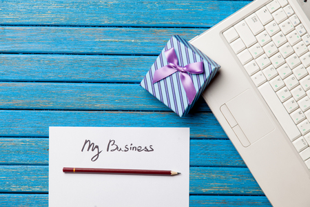 photo of paper My business, laptop and cute gift  on the wonderful blue wooden background