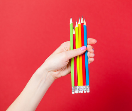 photo of female hand holding colorful pencils on the wonderful red background