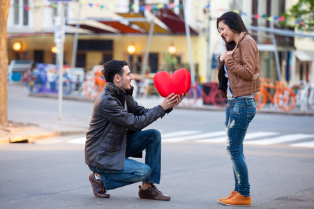 heart shaped: photo of cute couple with heart shaped toy on the wonderful street background