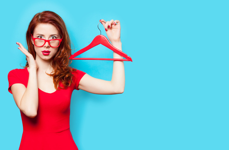 photo of beautiful young woman with hanger on the wonderful blue background Stock Photo