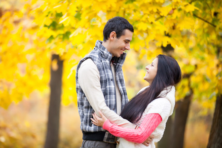 Photo Of Cute Couple Hugging On The Wonderful Yellow Trees Background Stock