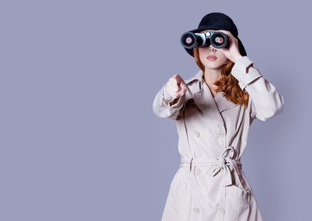 photo of beautiful young woman looking in binoculars on the wonderful grey studio background Stock Photo