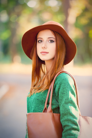 photo of beautiful young woman standing on the wonderful autumn park background