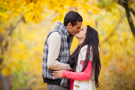 Photo Of Cute Couple Kissing On The Wonderful Autumn Park Background Stock