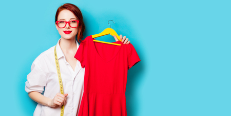 photo of beautiful young woman holding shirt on hanger on the wonderful blue studio background Stock Photo