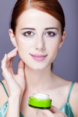 photo of beautiful young woman using her cream on the wonderful grey background