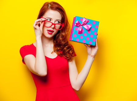 photo of beautiful young woman holding cute gift on the wonderful yellow studio background Stock Photo