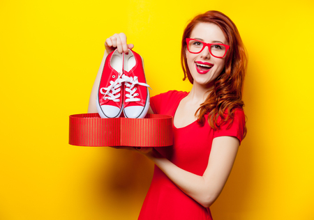 photo of beautiful young woman holding gumshoes under heart shaped box on the wonderful yellow studio background Stock Photo