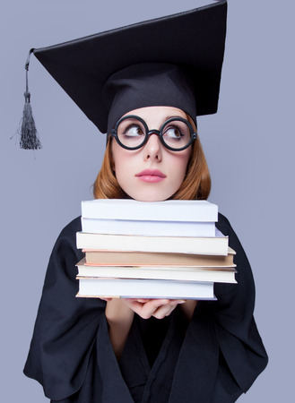 master degree: photo of beautiful young alumnus with pile of books on the wonderful grey studio background