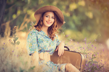 photo of beautiful young woman with suitcase sitting on the grass on the wonderful trees background Stock Photo