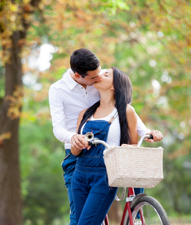 Photo Of Cute Couple Standing Near Bicycle And Kissing On The Wonderful Autumn Park Background Stock