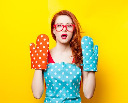 photo of beautiful young woman with potholders on the wonderful yellow studio background Stock Photo