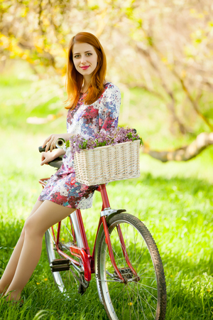 retro woman: photo of beautiful young woman with bicycle on the wonderful park background