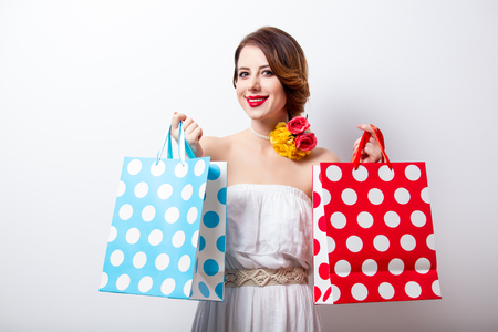 portrait of beautiful young woman with dotted shopping bags on the wonderful studio background