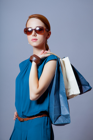 haircut: portrait of beautiful young woman with shopping bags on the wonderful grey studio background Stock Photo