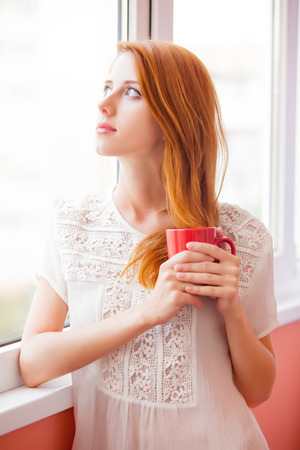 portrait of beautiful young woman with cup of coffee standing near the window