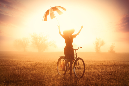 retro woman: photo of beautiful young woman on bicycle with umbrella on the wonderful sunset background