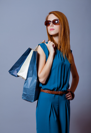 haircut: photo of beautiful young woman with shopping bags on the wonderful grey studio background Stock Photo