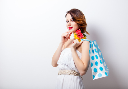 retro woman: portrait of beautiful young woman with dotted shopping bag on the wonderful studio background