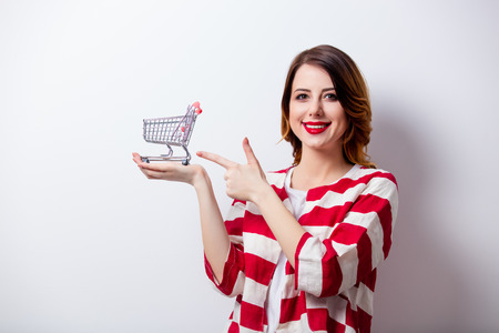 portrait of beautiful young woman with shopping cart on the wonderful white studio background