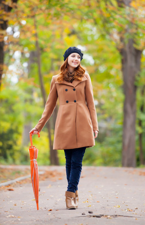 photo of beautiful young woman with umbrella on the wonderful autumn park background Stock Photo