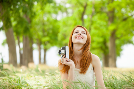 portrait of beautiful young woman holding retro camera on the wonderful park background Stock Photo