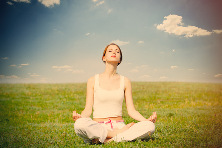 photo of beautiful young woman doing joga and relaxing on the wonderful field background Stock Photo