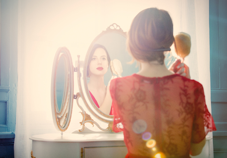 portrait of beautiful young woman with comb looking at herself in the wonderful mirror and sitting next to it