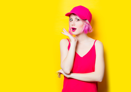 portrait of beautiful surprised young woman in cap on the wonderful yellow studio background Stock Photo