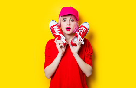 portrait of beautiful surprised young woman with red gumshoes on the wonderful yellow studio background