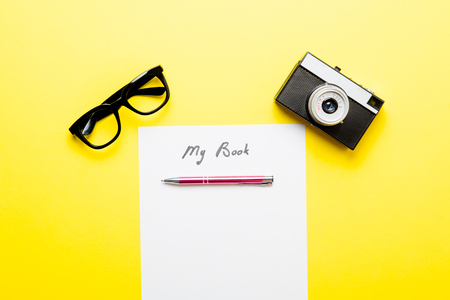 photo of sheet of paper My Book, retro camera, metallic pen and glasses on the wonderful yellow studio background Stock Photo