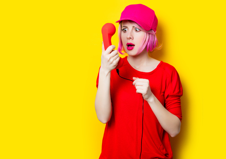 receiver: portrait of beautiful surprised young woman with red handset on the wonderful yellow studio background Stock Photo
