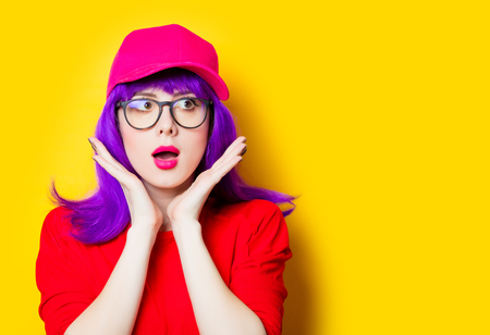 portrait of beautiful surprised young woman in cap and glasses on the wonderful yellow studio background