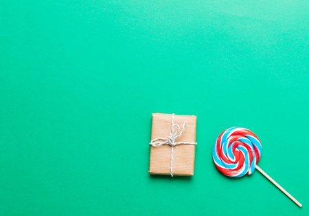 photo of colorful sweet lollipop and cute gift on the wonderful green studio background Stock Photo