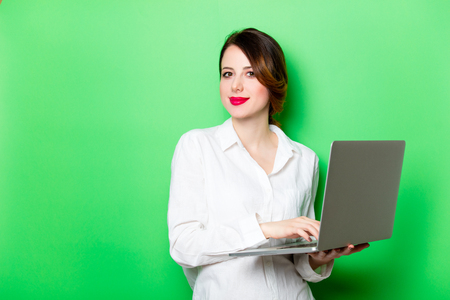 portrait of beautiful smiling young woman with laptop on the wonderful studio green background
