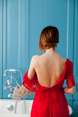 photo of beautiful young woman standing near bath and taking her dress off Reklamní fotografie